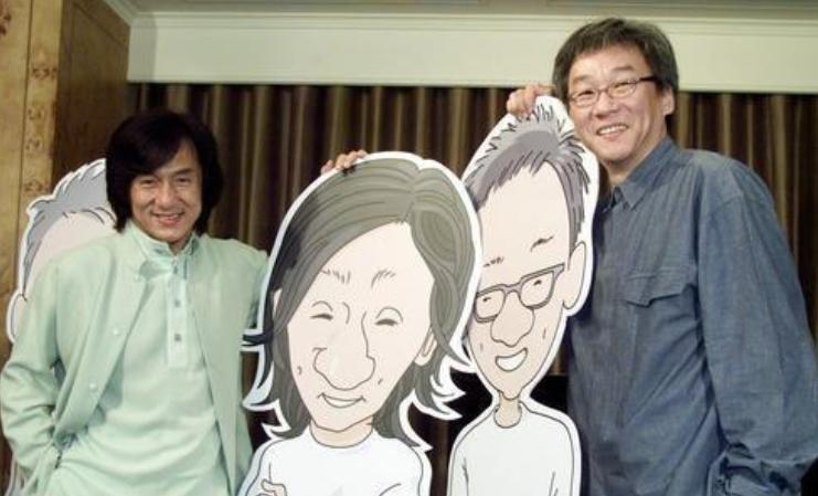 Jackie Chan und Edward Yang 2002 mit Entwürfen zu ihren Comic-Figuren; links hinter Jackie steht ein Willie Chan aus Pappe. Diese Figuren standen Jahre danach noch in Jackies Büro in Hongkong.